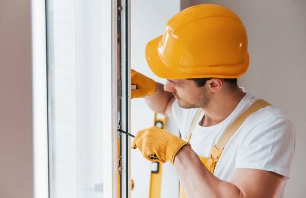handyman in yellow uniform installs new window hou JNGWHNV 1